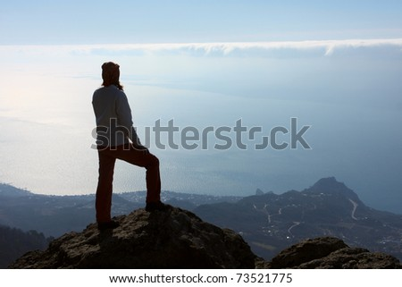 girl hiker standing on a rock and looking in the sky