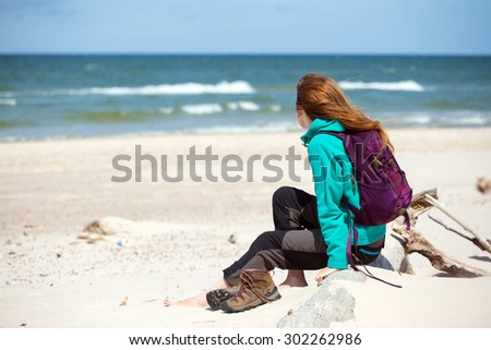 girl  hiker with a backpack sitting on the beach and looking at sea, Baltic Sea - stock photo