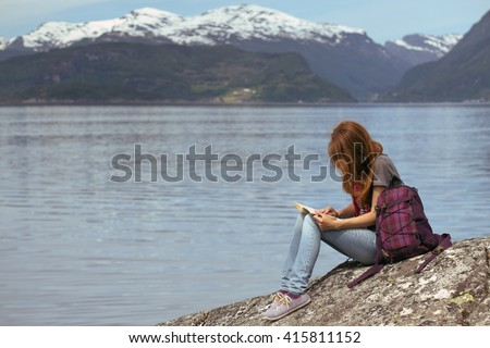 girl hiker with a book sitting on a rock on a background of mountains and lakes, norway