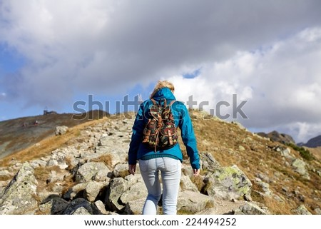 Girl hiker with backpacks standing on top of a mountain with great valley view, Tatra mountains, Poland, Slovakia - stock photo