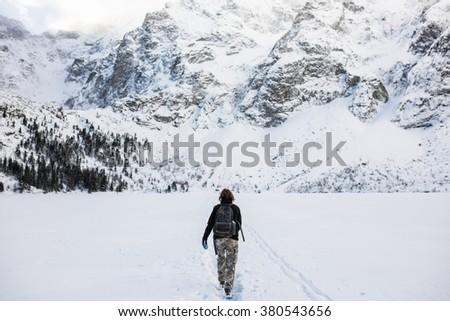 Girl hiking frozen lake. Winter high mountains in Europe. Five frozen Lakes Valley. Carpathians, The Tatra Mountains, The Miedziane Peak - 2233 m. - stock photo