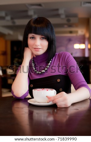 girl hold cup of coffee in hand looking straight - stock photo