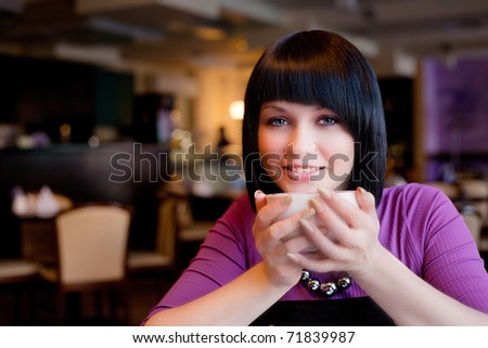 girl hold cup of coffee in hand smiling - stock photo