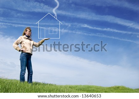 Girl hold dreaming house in the field - stock photo