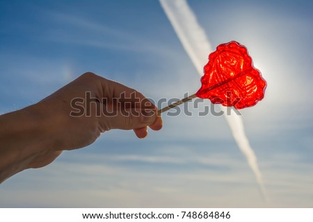Girl hold heart shaped red candy on stick. Sweet decorative food for Saint Valentines Day celebration. Valentin Day background.