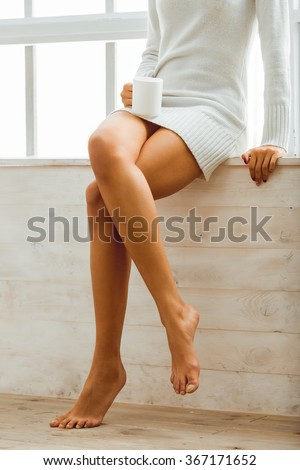 Girl hold in hands a cup sitting on a window-sill at home. Smooth legs African American women close - stock photo