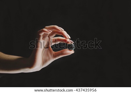 girl hold in her hand engagement ring on a black background