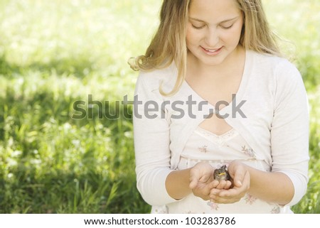 Girl holding a bird in her hands while sitting down on green grass in a home garden. - stock photo