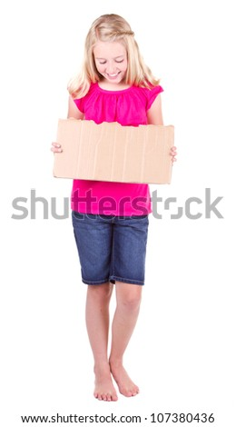 Girl holding a blank cardboard sign, looking down, isolated on white
