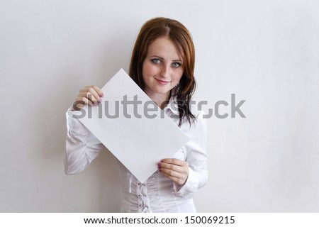 girl holding a blank sheet of paper with both hands and smiling