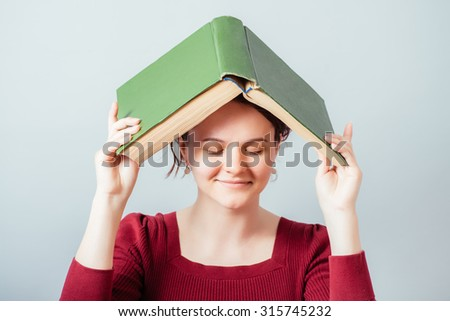 girl holding a book over his head - stock photo