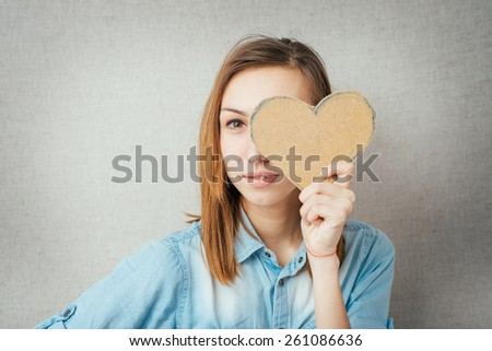 girl holding a cardboard paper heart - stock photo