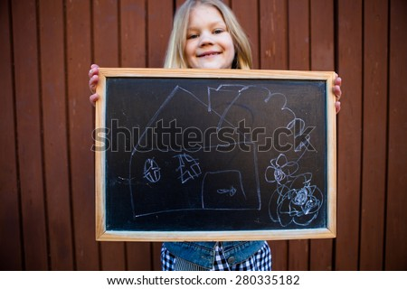 Girl holding a chalkboard with a picture of a house on it - stock photo