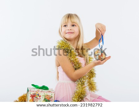 girl holding a Christmas toy ball - stock photo
