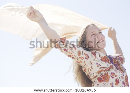 Girl holding a floating sarong in the air with arms outstretched against a blue sky. - stock photo
