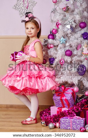 Girl holding a gift. Child wearing a dress and standing next to the Christmas tree. New Year. Holiday and fun. Merry Christmas. - stock photo