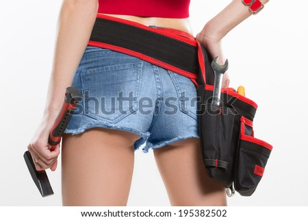 girl holding a hammer next to the booty. working ass - stock photo