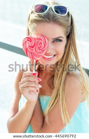 Girl holding a lollipop. Beautiful happy blond girl in the street. Young woman eating a piece of candy. - stock photo