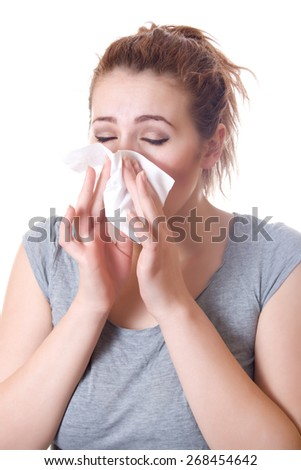 Girl holding a napkin in the nose sneezing, allergies, colds