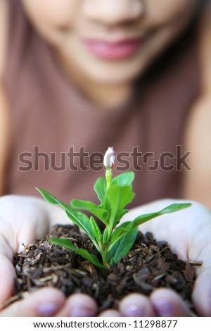 Girl holding a new flower - stock photo