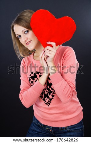 girl holding a red heart on a black background - stock photo