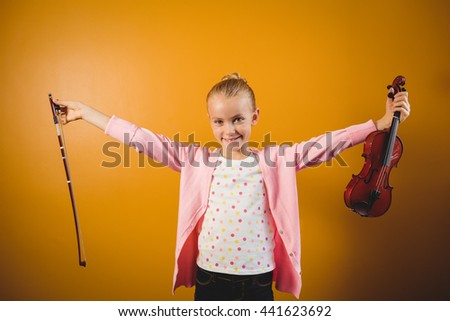Girl holding a violin on yellow background