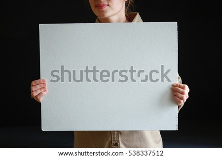 girl holding a white canvas