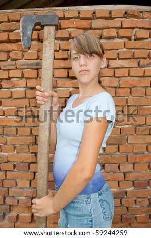 Girl holding ax in front of the brick wall - stock photo