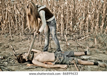 Girl holding axe on the boy neck, and blood on the his chest - stock photo