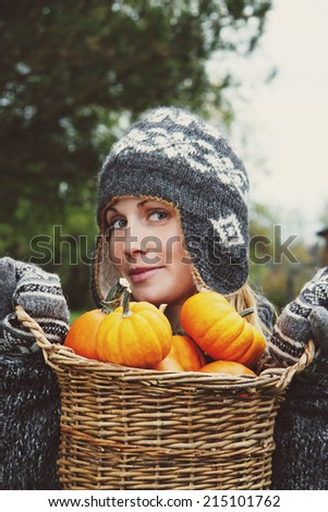 Girl holding basket of pumpkins for Thanksgiving