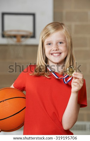 Girl Holding Basketball And Medal In School Gymnasium - stock photo