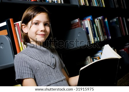Girl holding book reading in Library - stock photo