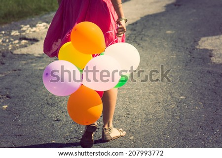 girl holding bunch of colorful air balloons - stock photo