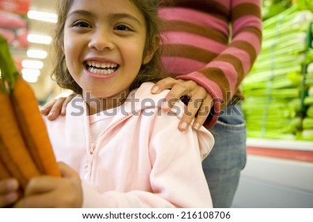 Girl holding carrots in grocery store - stock photo