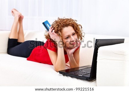 Girl holding credit card in front of her laptop while dreaming