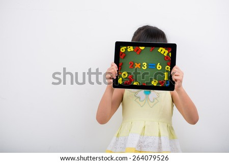 Girl holding digital tablet with math example in front of her face: technology in education concept - stock photo