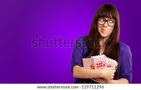 Girl Holding Empty Popcorn Packet Isolated On Purple Background - stock photo