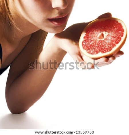 Girl holding grapefruit half - stock photo