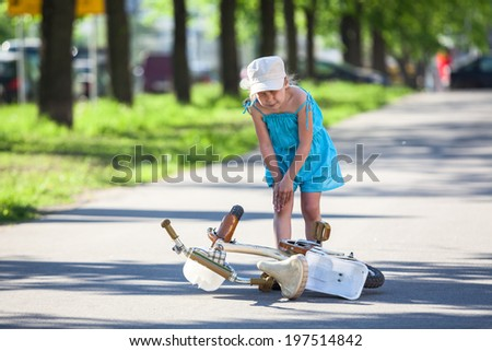 Girl holding her knee after falling down - stock photo