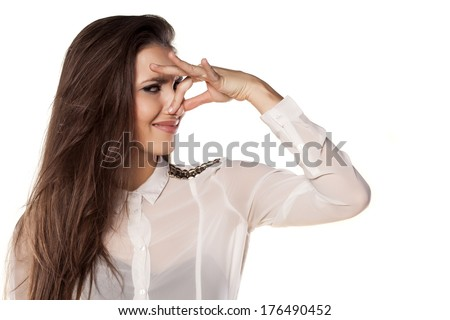 girl holding her nose to her toes because of the odor - stock photo