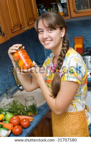 Girl holding jar with vegetables in the kitchen