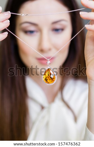 Girl holding necklace with yellow sapphire at jeweler's shop. Concept of wealth and luxurious life - stock photo