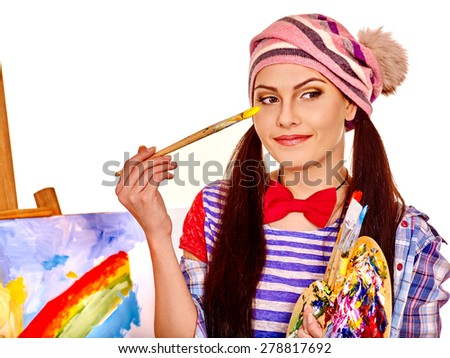 Girl  holding one hand on background of easel. Isolated. - stock photo