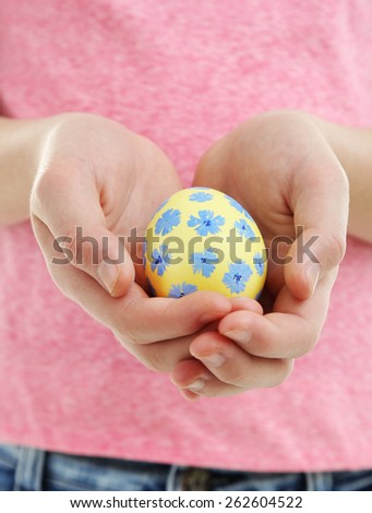 Girl holding painted egg in her hands, close-up - stock photo