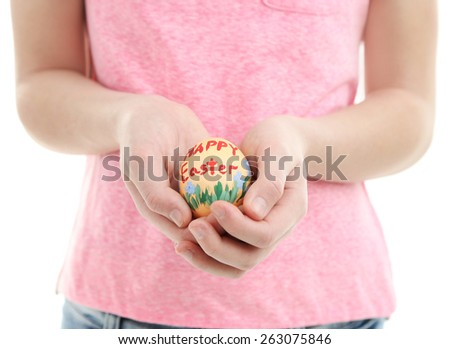 Girl holding painted egg in her hands, close-up, isolated on white - stock photo