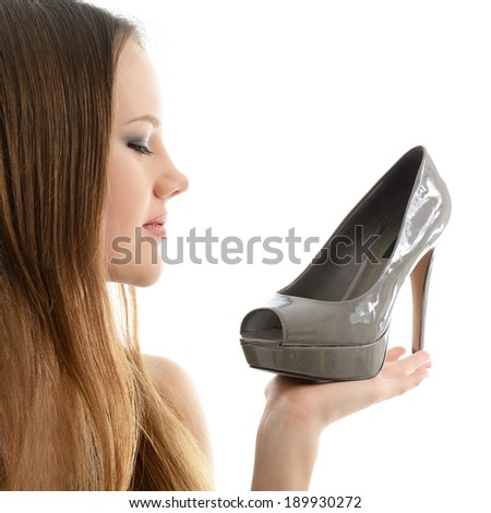 Girl holding shoe in hand an looking with love on it, over white background. - stock photo