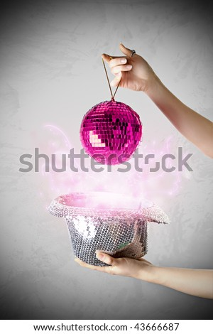 Girl holding silver hat and pink disco ball with lighting effect. Concept of glamor, party, entertainment, fun, night live