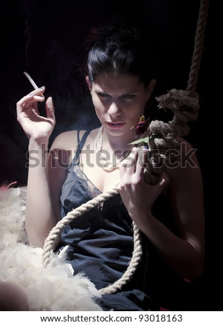 Girl holding the cigarette in one hand and rope with rose  in other/Suicide Thoughts - stock photo