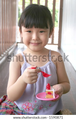 girl holding toy fork & cake - stock photo
