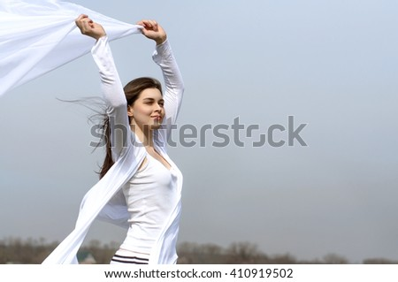Girl holds fabric in hands waving in the wind against the blue sky. She is wearing in a white loose-fitting clothing. Concept: ease, health, cleanliness.